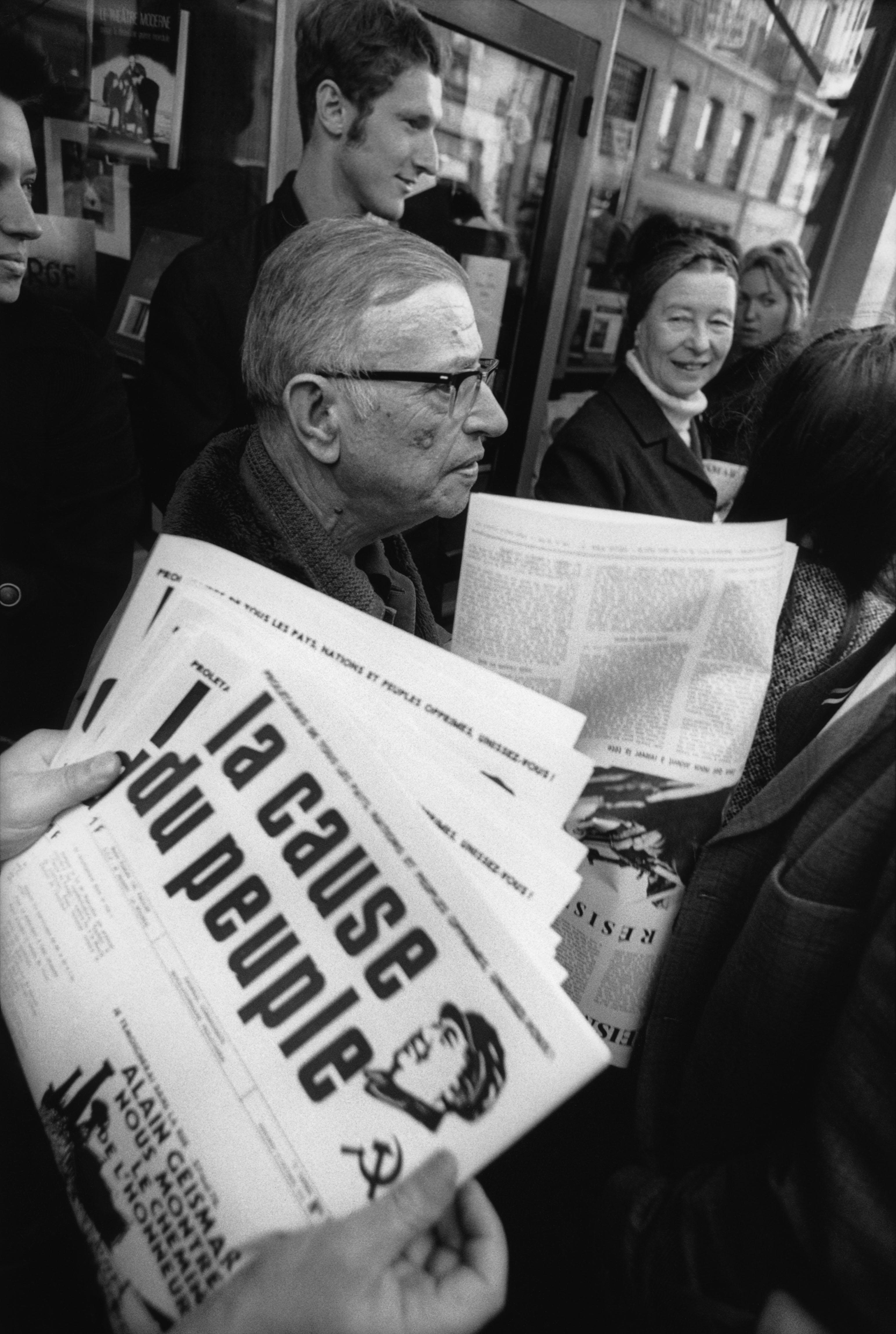 """1970 FRANCE. Paris. 1970. Jean-Paul SARTRE et d'autres intellectuels tiennent une conférence de presse à l'imprimerie de """"La cause du Peuple"""", pour soutenir le journal qu'ils sortent vendre dans la rue.  SARTRE et Simone de BEAUVOIR, écrivain français.  Image autorisée à Caroline Chang L&PM Editores par Caroline Chang Conditions d'utilisation :  - 3000 X 3000 pixels (A4)  © Bruno Barbey / Magnum Photos"""